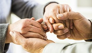 Hands reaching out between two people and clasping each other