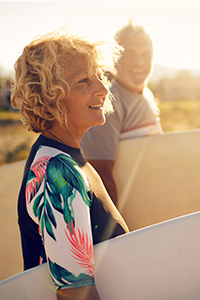Mature lady holding a surf board