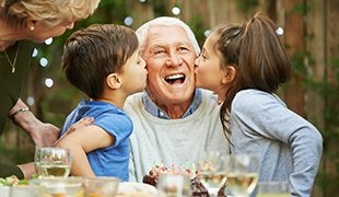 children happily kissing their grandfather