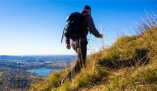 Man hiking up picturesque hillside with views