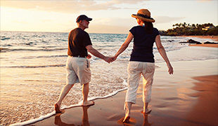 Couple in hats holding hand and walking in the surf of a beach
