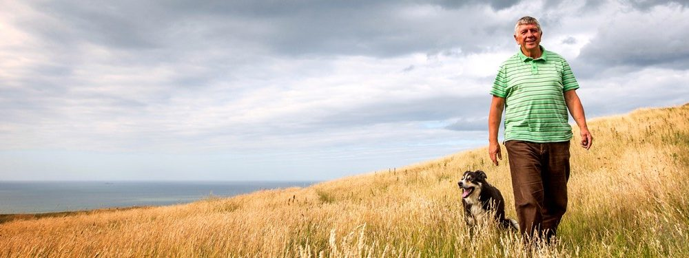 Man walking his dog in a field of long grass