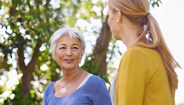 Senior woman chatting with another lady in a woodland