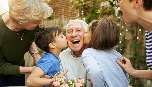 Grandfather being kissed on either cheek by two grandchildren